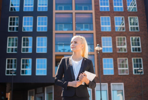 woman standing in front of building development carrying papers