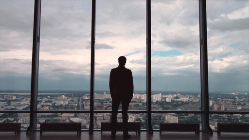 Rear view of businessman in an office with panoramic city view